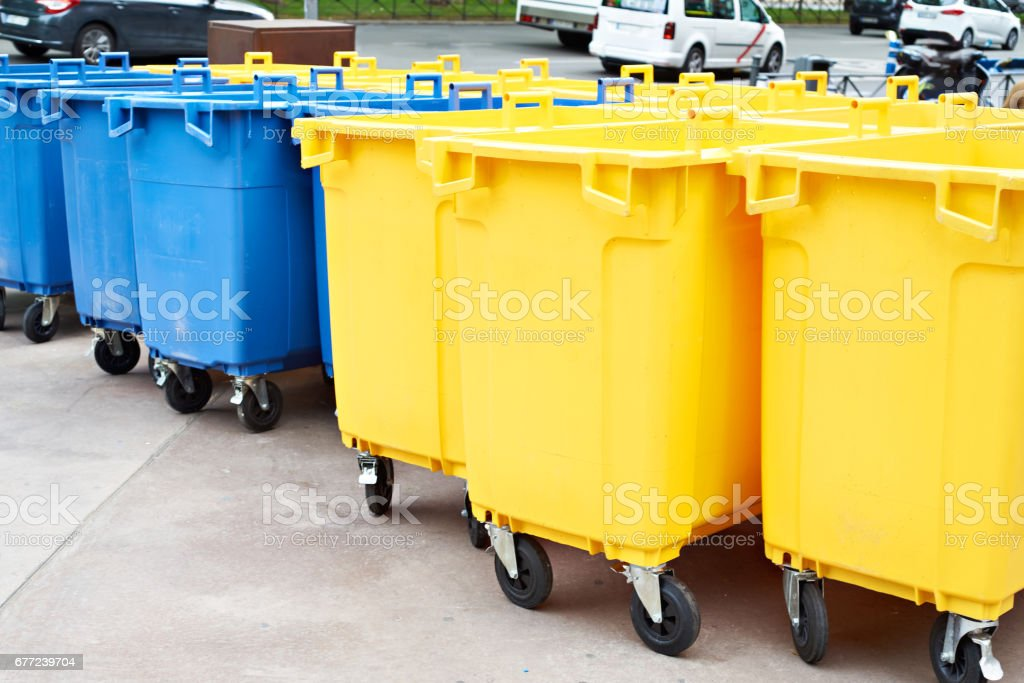 Yellow and blue plastic garbage cans on city street stock photo