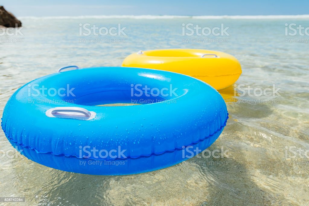 Yellow and blue rubber ring floating on clear blue sea, Cornwall. stock photo