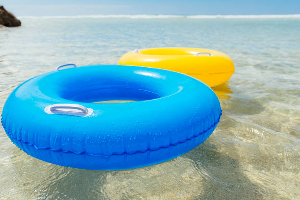 yellow and blue rubber ring floating on clear blue sea, cornwall. - rubber ring stock photos and pictures
