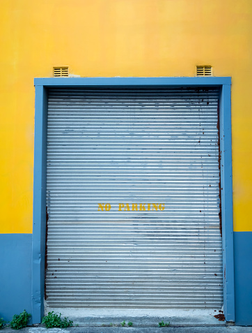 Yellow and blue wall with silver metal roller door with stencil NO PARKING