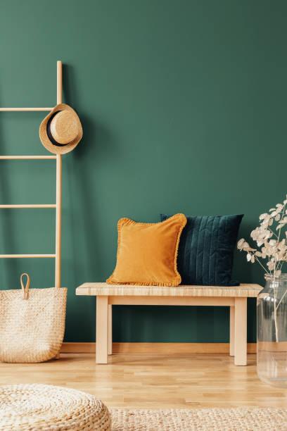 gelben und grünen kissen auf den couchtisch aus holz auf natürliche gestaltete innenraum, echtes foto mit textfreiraum auf leere grüne wand - kissen grün stock-fotos und bilder