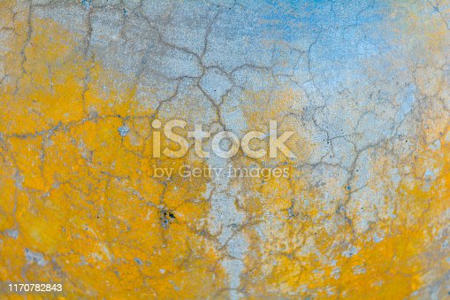 Yellow and gray cracked concrete texture. Rough surface with yellow painted spots. Old weathered painted background texture