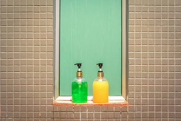 yellow and green bottles of liquid soap and shampoo - dusch accessoires stock-fotos und bilder