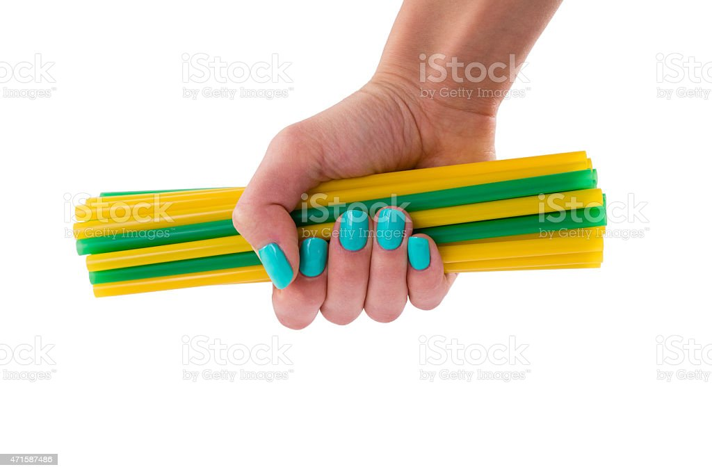 Yellow and green cocktail stick in a female hand stock photo