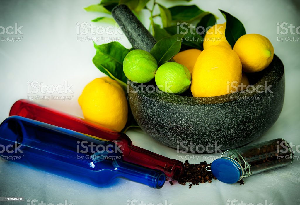 yellow and green lemons in a bowl with colored bottles stock photo