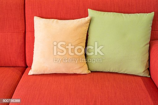 yellow and green pillows on red sofa