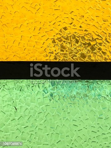 Surface of a stained glass window with a black metal divider. Yellow on one side and green on the other. Typical vintage old window in Brazil.