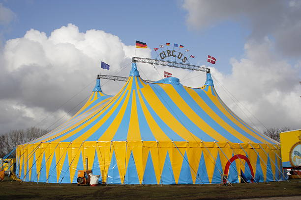 Yellow and light blue circus tent over a cloudy sky Focus on the blue and yellow Circus tent in windy weather! pejft stock pictures, royalty-free photos & images