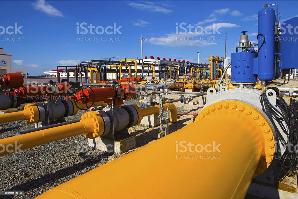 Yellow and orange pipe and valves at an industrial plant stock photo