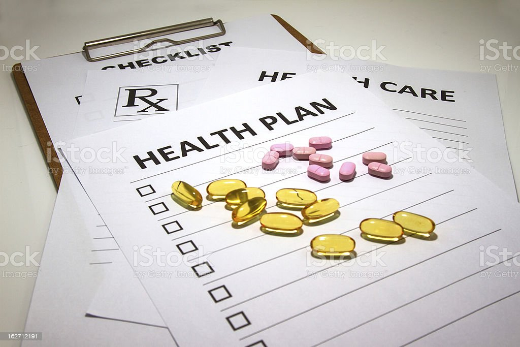 Yellow and pink pills scattered across health care forms stock photo
