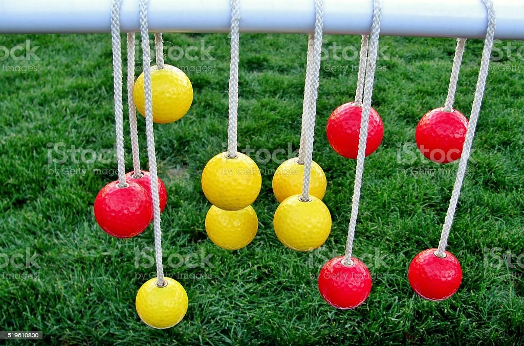 Yellow and red balls hanging on the ropes stock photo