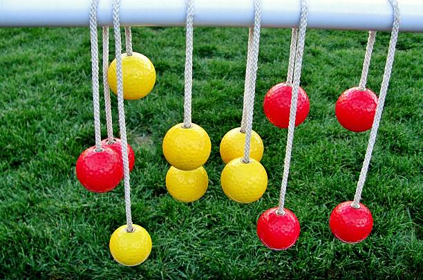 yellow and red balls hanging on the ropes - ladder stockfoto's en -beelden