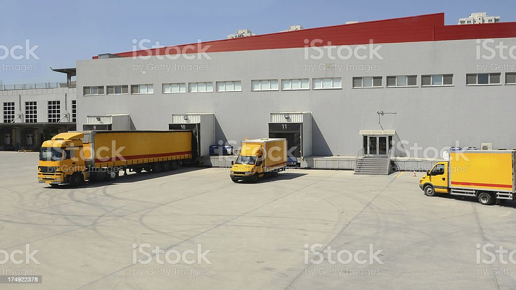 Yellow and red freight trucks loading at a grey warehouse  stock photo