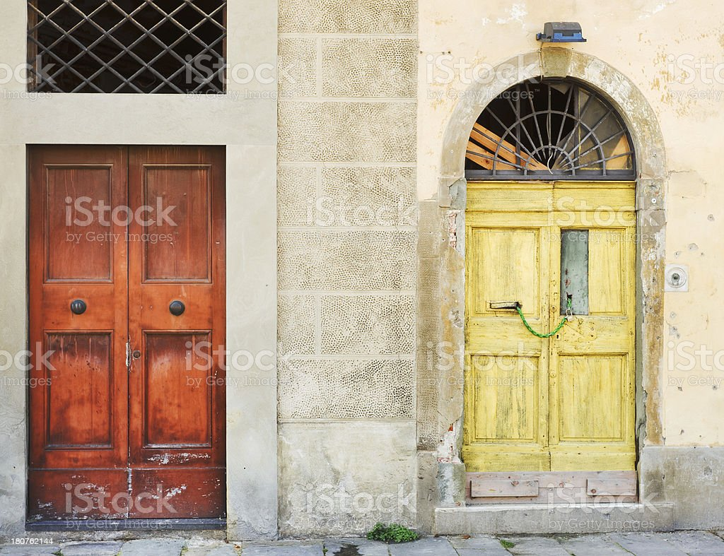 Yellow and red front door entrances, weathered Photographed in Pisa, Italy. Architectural Feature Stock Photo