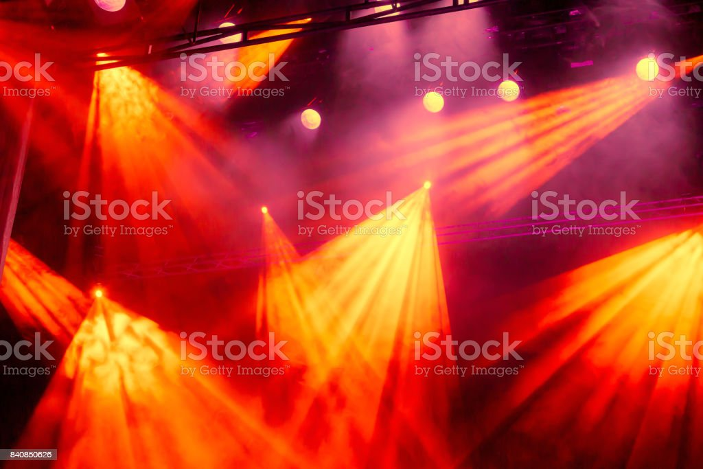 Yellow and red light rays from the spotlight through the smoke at the...