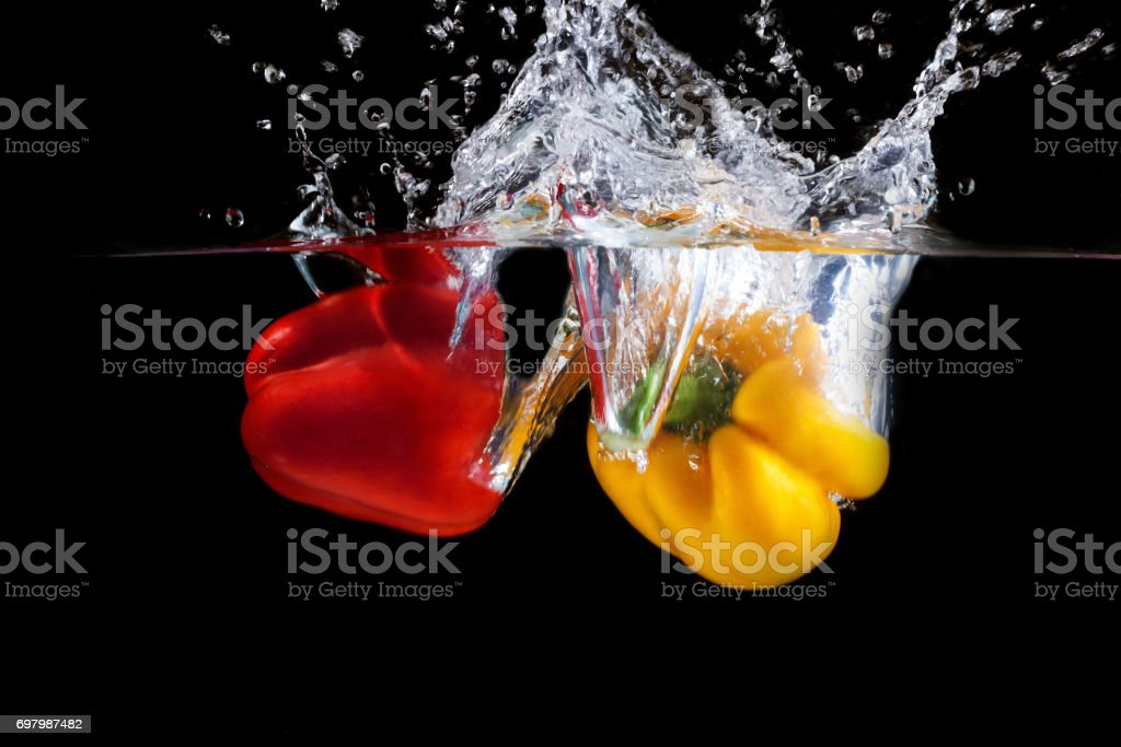 Yellow and red pepper falling into water and splashing against black...