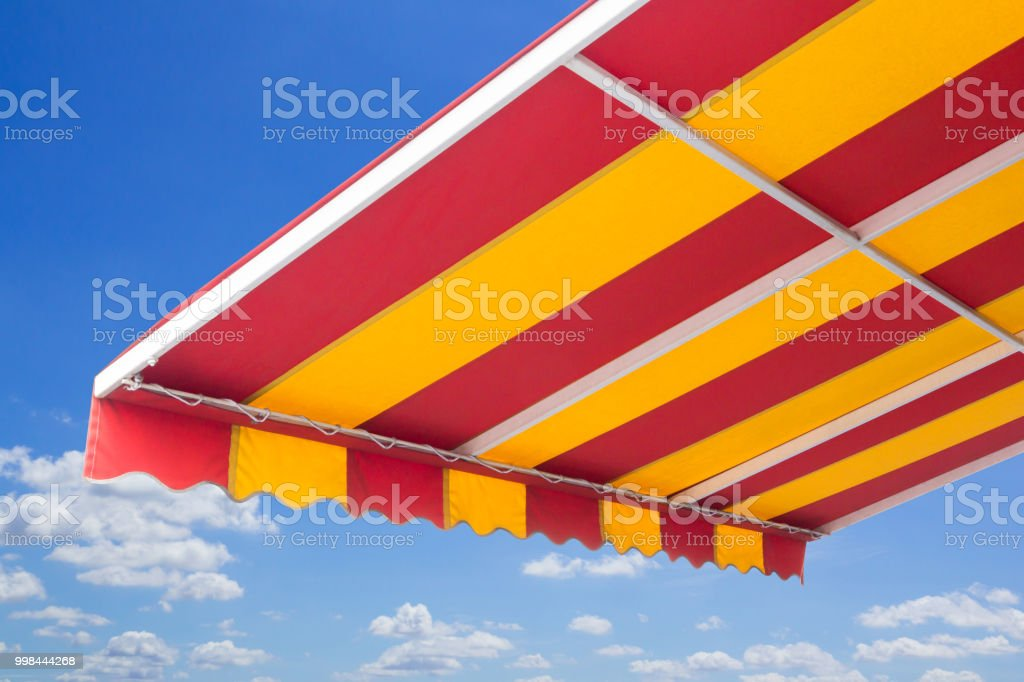 yellow and red striped awning with steel structure, blue sky and white  cloud background '