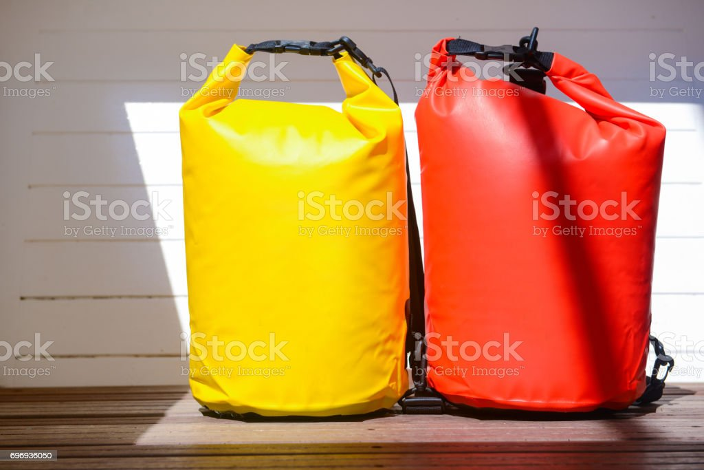 yellow and red waterproof bag for travel at the sea stock photo