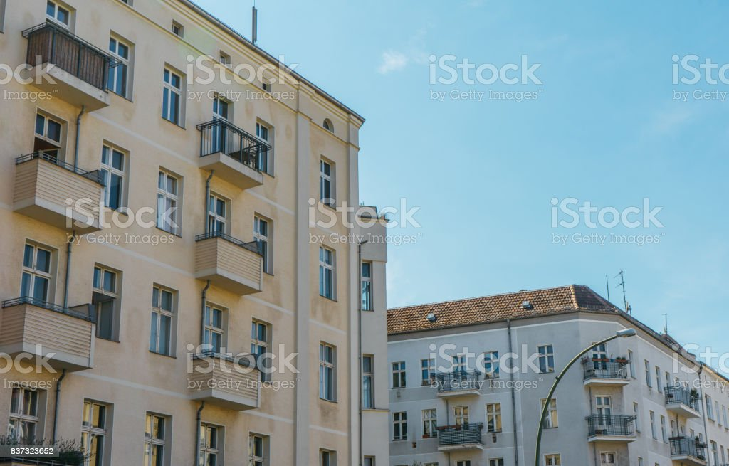 yellow and white corner houses in a row at berlin stock photo