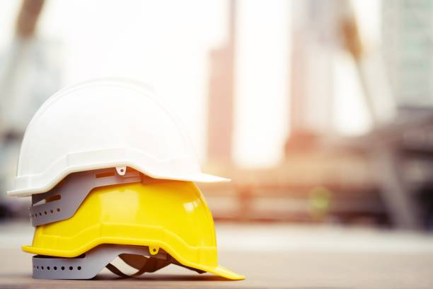 yellow and white hard safety wear helmet hat in the project at construction site building on concrete floor on city with sunlight. helmet for workman as engineer or worker. concept safety first. - kask budowlany zdjęcia i obrazy z banku zdjęć