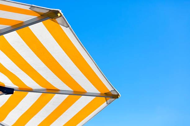 gelbe und weiße gerührt regenschirm gegen blauen himmel, textfreiraum - outdoor sonnenschutz stock-fotos und bilder