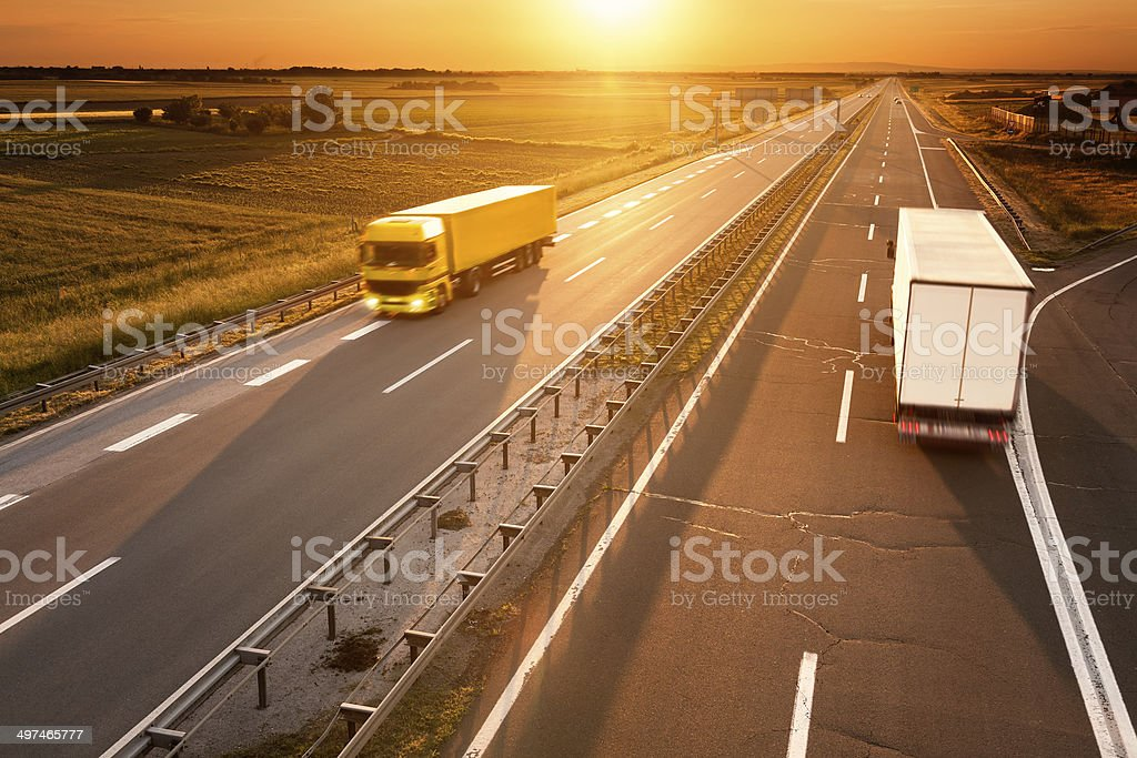 Yellow and white truck in motion blur on the highway Yellow and white truck in motion blur on the highway at sunset Activity Stock Photo