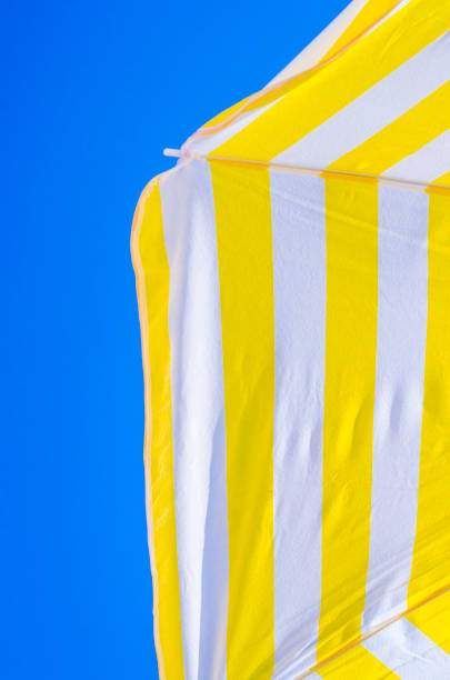 yellow and white umbrellas with the blue sky in the background, symbols of summer stock photo