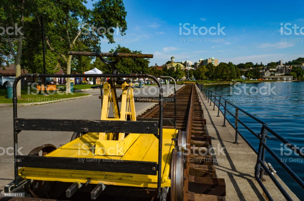 Yellow antique hand power railcar next to the St. Lawrence River  on tracks leading to Brockville railway tunnel. with a blue summer sky and the city of Brockville in the background stock photo