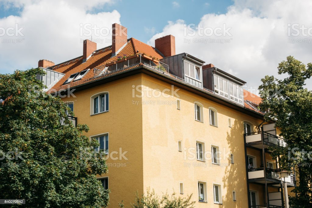 yellow apartment building with chimneys stock photo