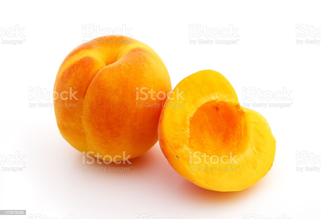Yellow apricot and a sliced half over a white background stock photo