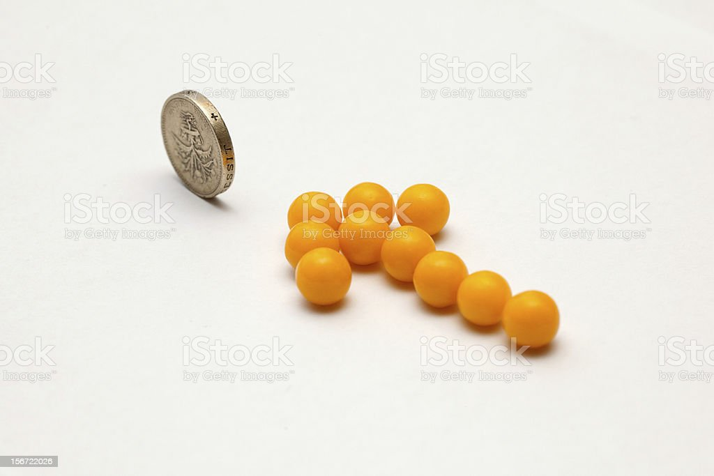 Yellow arrow of pills pointing on one pound coin royalty-free stock photo