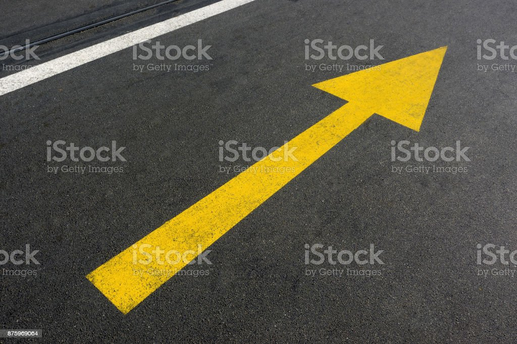 Yellow arrow on an empty asphalt road stock photo