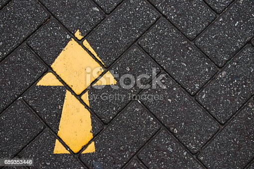 istock Yellow arrow paint on black brick concrete background 689353446