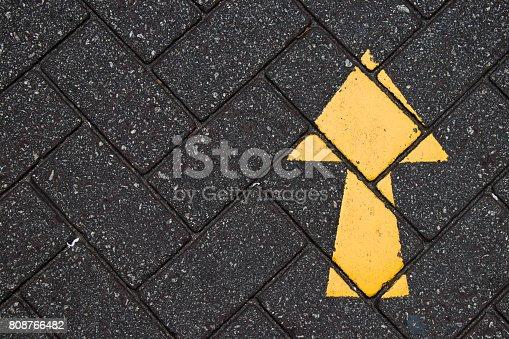 istock Yellow arrow paint on black brick concrete background 808766482