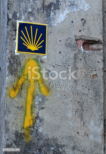 istock Yellow arrow painted in a wall. Directional sign for pilgrims in Saint james way. Camino de Santiago, Galicia, Spain 938506086