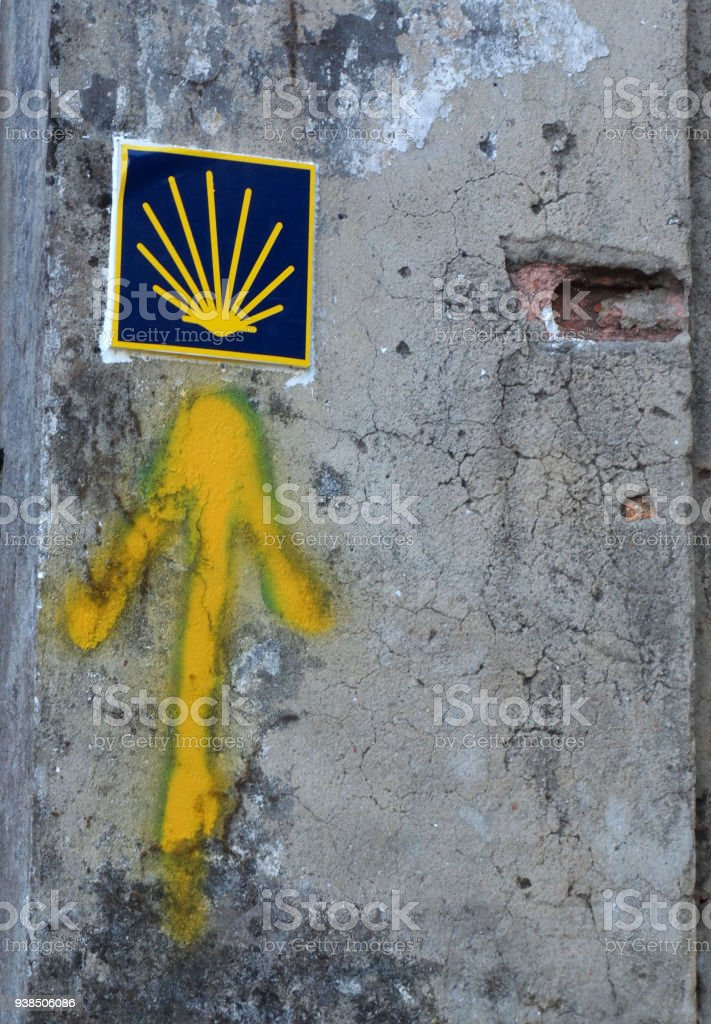 Yellow arrow painted in a wall. Directional sign for pilgrims in Saint james way. Camino de Santiago, Galicia, Spain stock photo