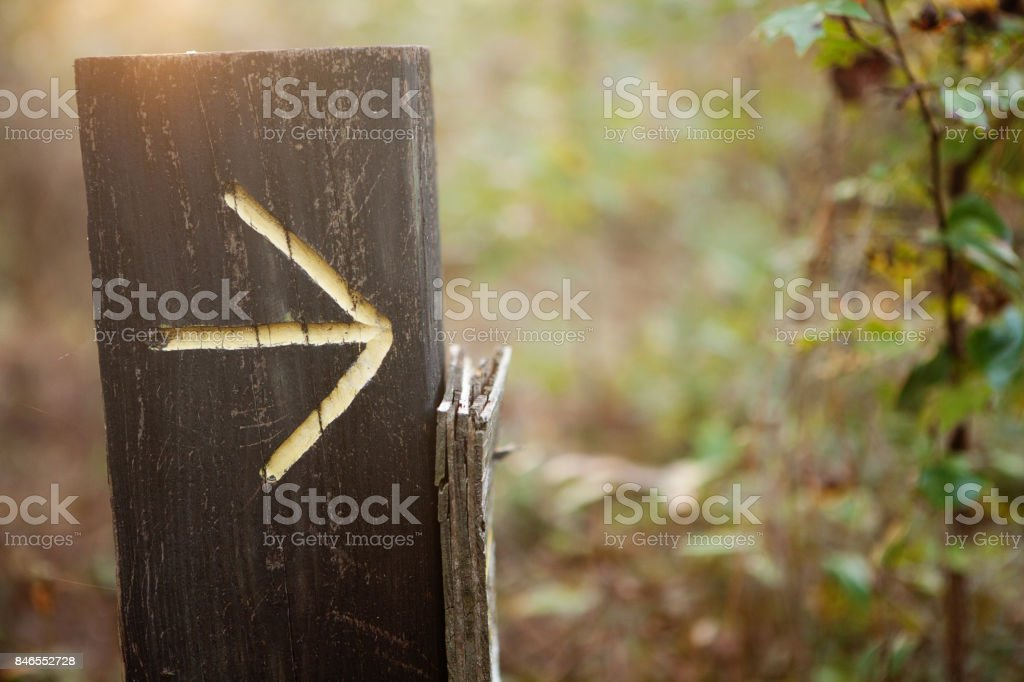 Yellow arrow pointing right on a wood post stock photo