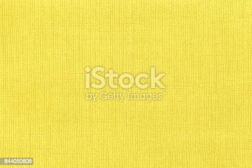 Light yellow background from a textile material with pattern, closeup. Structure of the lemon fabric with natural texture. Cloth backdrop.