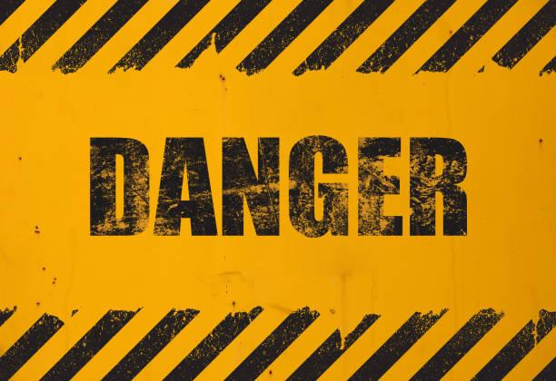 黒いグランジの危険な看板を持つ黄色の背景 - 危険物 ストックフォトと画像