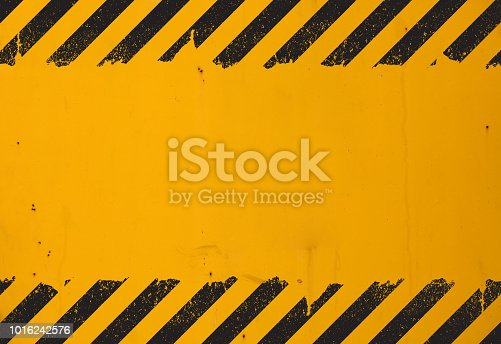 Old yellow weathered painted background with grunge black hazard sign stripes and copy space