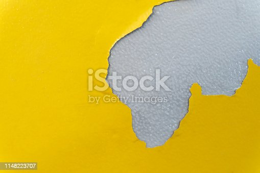 1084390994istockphoto Yellow background with peeling color, Color cracks on yellow plastic 1148223707