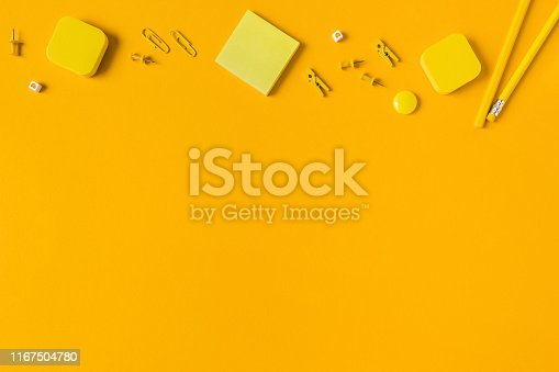 istock Yellow background with scattered writing materials. 1167504780