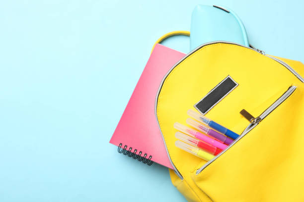 yellow backpack with different school supplies stock photo