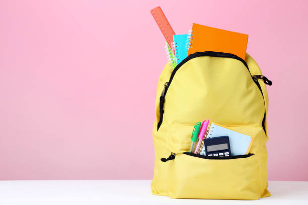yellow backpack with school supplies on pink background - cartella scolastica foto e immagini stock
