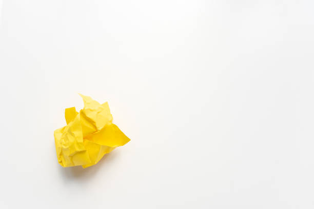 Yellow ball of paper on white background stock photo