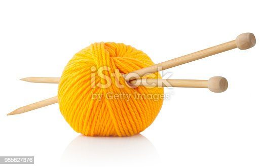 Yellow ball of wool with knitting needles on white background.