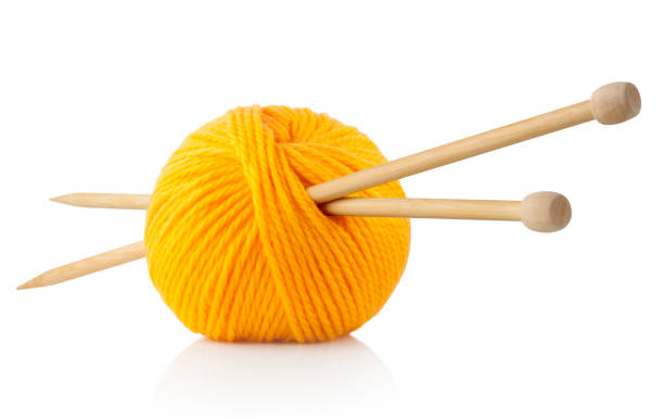 Yellow ball of wool with knitting needles stock photo