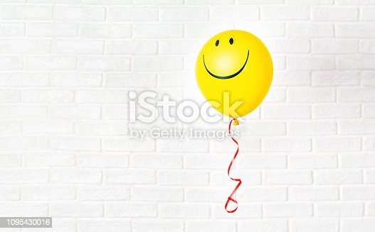 istock Yellow ballon with smile hangs aganst white wall 1095430016