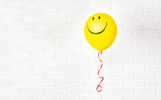 yellow ballon with smile hangs aganst white wall - alegria imagens e fotografias de stock