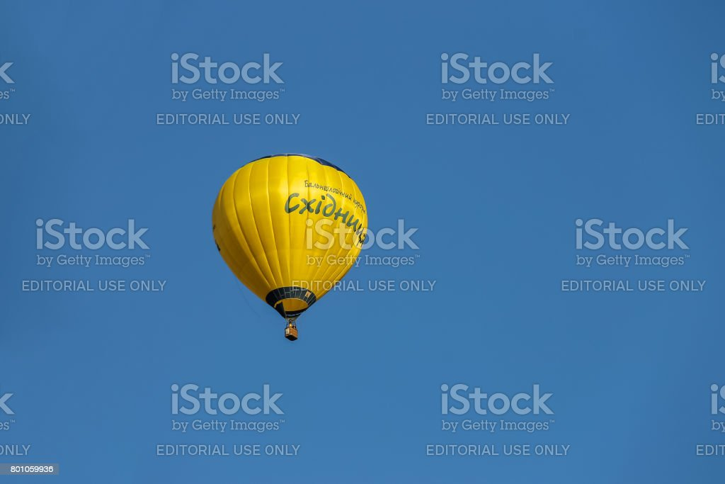 Yellow balloon in blue sky in Schodnica, Ukraine stock photo